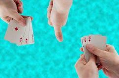 Spielkarten in der Hand auf dem Hintergrund des Wassers stockbild