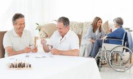 Spielkarten der Männer, während ihre wifes sprechen Stockbild