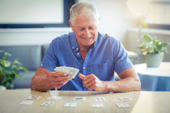Spielkarten des älteren Mannes im Wohnzimmer stockbilder