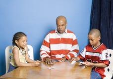 Spielkarten des Mannes mit seinen Kindern lizenzfreie stockfotos