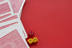 Spielkarten und würfelt auf rotem Hintergrund Stockfoto
