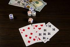 Spielkarten, Würfel und Dollar auf einer Tabelle Stockfoto