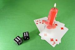 Spielkarten, Würfel und eine Kerze Stockbild
