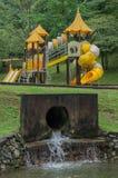 Spielplatz mit Abwasserkanalabfluß im foeground Stockfotografie