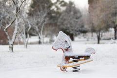 Spielplatzgeräteschaukelpferd bedeckt im Schnee stockfotografie