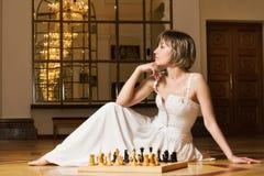 Spielschach der jungen Frau im reichen Innenraum Lizenzfreie Stockbilder