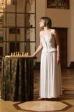 Spielschach der jungen Frau im reichen Innenraum Stockbild