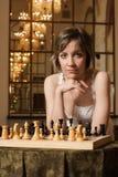 Spielschach der jungen Frau im reichen Innenraum Stockfotos