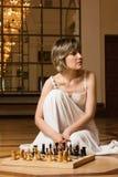Spielschach der jungen Frau im reichen Innenraum Stockfoto