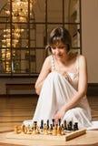 Spielschach der jungen Frau im reichen Innenraum Lizenzfreie Stockfotografie