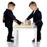 Spielschach mit zwei kleinen Jungen lizenzfreie stockfotos