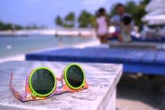 Spielsonnenbrillen am Strand Stockbilder