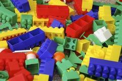 Spielt die Sammlung, die auf weißem Hintergrund lokalisiert wird Multi farbiger Plastikerbauer mit Blöcken für errichtende Häuser Lizenzfreies Stockbild