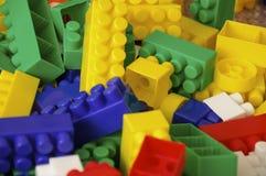 Spielt die Sammlung, die auf weißem Hintergrund lokalisiert wird Multi farbiger Plastikerbauer mit Blöcken für errichtende Häuser Stockfoto