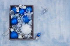 Spielt gesetzte Silberweiß- und Blaubälle der Weihnachtspostkartendekoration Kegelgeschenke in der Holzkiste Lizenzfreies Stockbild