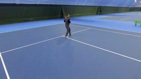Spieltennis des jungen Mannes am Tennisplatz stock video footage
