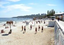 Spielvolleyball der jungen Leute auf Sandstrand Lizenzfreie Stockfotos