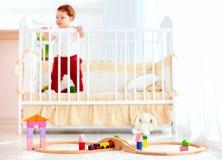 Spielwaren auf dem Boden im sonnigen Schlafzimmer mit Säuglingsbaby in der Krippe auf Hintergrund Stockfoto
