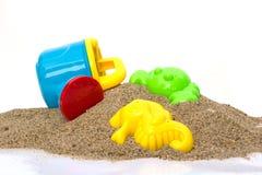 Spielwaren auf Sand mit weißem Hintergrund. Lizenzfreies Stockbild