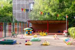 Spielwaren auf sandigem Spielplatz des Kindergartens Stockbild