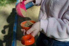 Spielwaren für den Sandkasten in den Händen der Kinder stockbilder