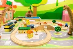 Spielwaren für Kinder, Dinosaurier, die Kind-` s Eisenbahn-Struktur betrachten Stockfotos