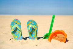 Spielwaren und Flipflops am Strand Lizenzfreie Stockbilder