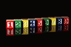 Spielwaren und Spiele Hölzerne Würfel mit Zahlen lokalisiert auf Schwarzrückseite stockbild
