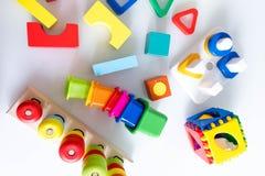 Spielwarenkinderhintergrund Hölzerne Würfel mit Zahlen und bunte Spielzeugziegelsteine auf einem weißen Hintergrund Rahmen gemach Stockbild