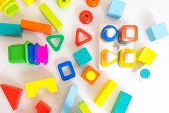Spielwarenkinderhintergrund Hölzerne Würfel mit Zahlen und bunte Spielzeugziegelsteine auf einem weißen Hintergrund Rahmen gemach Lizenzfreie Stockbilder