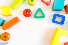 Spielwarenkinderhintergrund Hölzerne Würfel mit Zahlen und bunte Spielzeugziegelsteine auf einem weißen Hintergrund Rahmen gemach Lizenzfreies Stockfoto