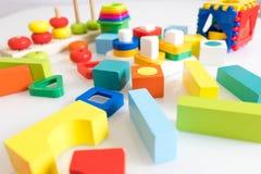 Spielwarenkinderhintergrund Hölzerne Würfel mit Zahlen und bunte Spielzeugziegelsteine auf einem weißen Hintergrund Rahmen gemach Lizenzfreie Stockfotos
