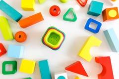 Spielwarenkinderhintergrund Hölzerne Würfel mit Zahlen und bunte Spielzeugziegelsteine auf einem weißen Hintergrund Rahmen gemach Stockbilder
