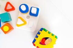 Spielwarenkinderhintergrund Hölzerne Würfel mit Zahlen und bunte Spielzeugziegelsteine auf einem weißen Hintergrund Rahmen gemach Stockfoto