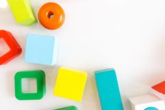 Spielwarenkinderhintergrund Hölzerne Würfel mit Zahlen und bunte Spielzeugziegelsteine auf einem weißen Hintergrund Rahmen gemach Lizenzfreies Stockbild