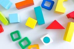 Spielwarenkinderhintergrund Hölzerne Würfel mit Zahlen und bunte Spielzeugziegelsteine auf einem weißen Hintergrund Rahmen gemach Stockfotografie