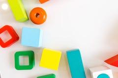 Spielwarenkinderhintergrund Hölzerne Würfel mit Zahlen und bunte Spielzeugziegelsteine auf einem weißen Hintergrund Rahmen gemach Lizenzfreie Stockfotografie
