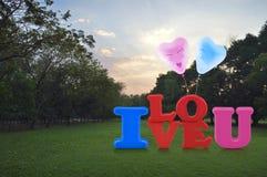 Spielzeug des Alphabetes ich liebe dich mit glücklichem Liebesherzballon im Park Lizenzfreie Stockfotos