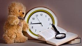 Spielzeug - ein Bärenjunges vor Uhr nahe dem Buch Stockbild