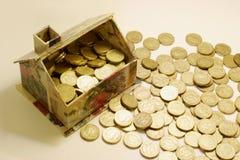 Spielzeug-Haus und Münzen Lizenzfreies Stockbild