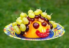 Spielzeug hergestellt von der Frucht auf grünem Hintergrund Stockfotos