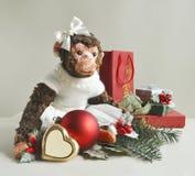 Spielzeugaffe mit Weihnachtsdekorationen und -geschenken Lizenzfreies Stockfoto