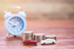 Spielzeugauto, Wecker und Münzenstapel auf hölzernem Tabellenhintergrund stockbild