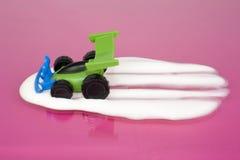 Spielzeugautofahren durch Milch Stockbilder
