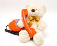 Spielzeugbär mit altem Telefon Stockbild
