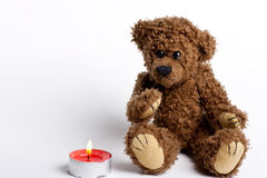 Spielzeugbär Teddybär und brennende Kerze. Lizenzfreies Stockfoto
