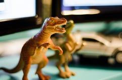 Spielzeugdinosaurier mit verwischt anderen Spielwaren im Hintergrund lizenzfreie stockbilder