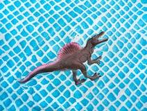 Spielzeugdinosaurier Stegosaurus, der in das Wasser im Pool auf Sommer schwimmt stockfotografie