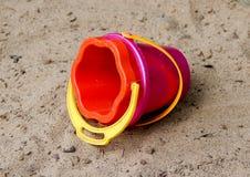 Spielzeugeimer auf dem Sand Stockfotos