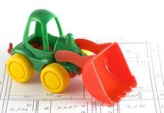 Spielzeugexkavator auf einem Plan Stockfoto